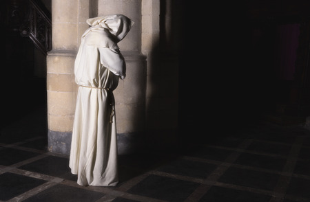 Lonely monk standing at a pillar in a dark medieval church