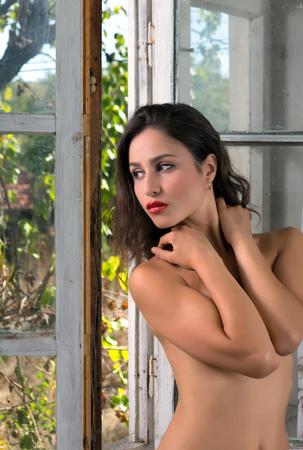 mujeres jovenes desnudas: Mujer joven en topless de pie en la ventana de una habitación abandonada