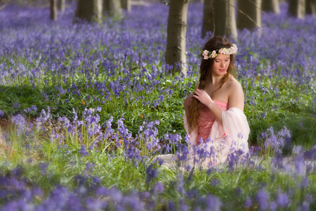 Innocent young woman with pink fairy dress in a springtime bluebells forest Stock Photo