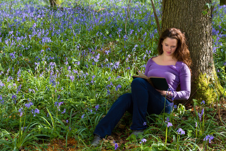 millions: Attractive young woman among millions of bluebells wildflowers Stock Photo