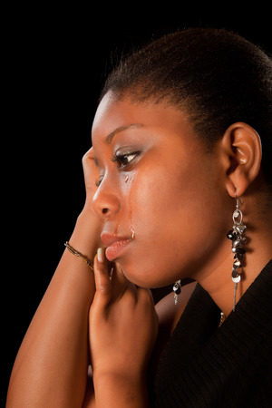 Crying african ghanese young woman shedding tears