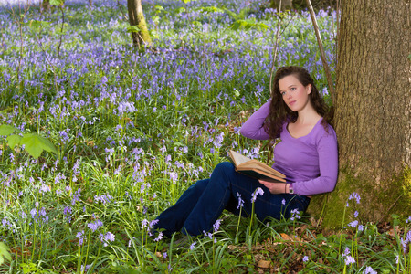 Young woman sitting under a tree in a springtime bluebells forest photo
