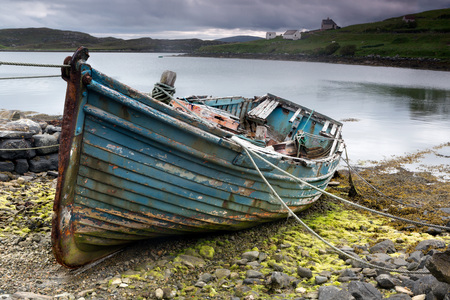 Weathered fishing boat lying on a rocky beach on the Isle of Lewis, Outer Hebrides, Scotland Archivio Fotografico