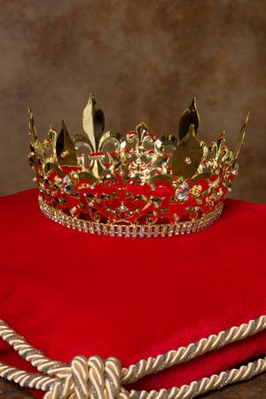 regalia: Medieval golden kings crown on red velvet pillow