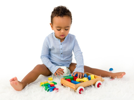 Young 18 month old toddler boy playing with wooden colorful blocks photo