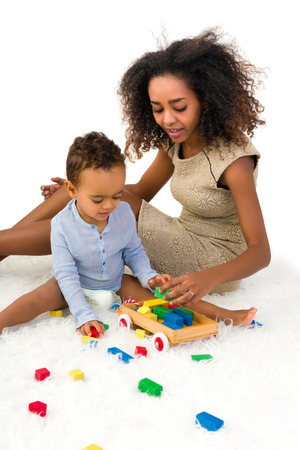 Cute African toddler boy playing with colorful wooden blocks