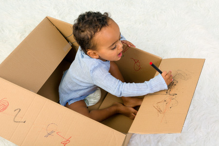 pencil box: Mixed race little toddler boy sitting in a cardboard box playing with crayons Stock Photo