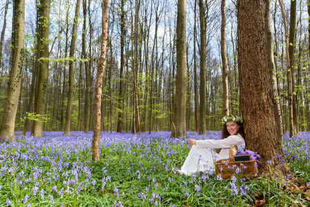 Victorian woman in white dress in a springtime bluebells forest photo