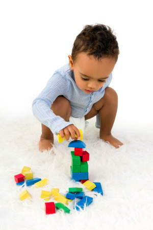 Young 18 month old toddler boy playing with wooden colorful blocks