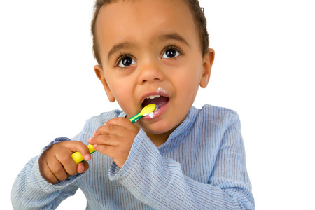 Glimlachend 18e maand oude Afrikaanse peuter jongen zijn tanden poetsen Stockfoto