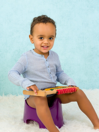 urinating: Potty training of a cute African toddler boy playing with an abacus