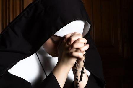 monasteri: Ritratto di arti di una suora novizia in profonda preghiera con il rosario Archivio Fotografico