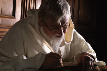 franciscan: Bearded monk writing with a quill in a dark church