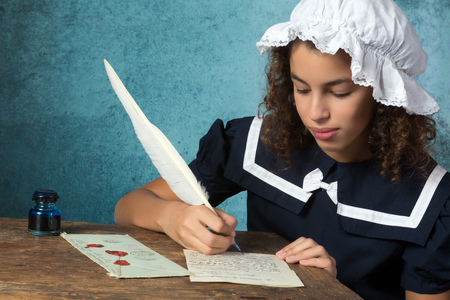 Young victorian girl in vintage dress and bonnet writing a letter Stock Photo