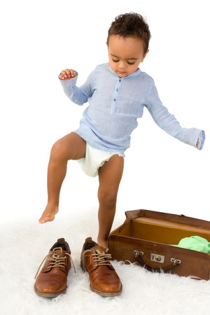 Playful African toddler boy having fun with Dads shoes Stock Photo