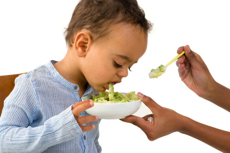 revulsion: Little 18 month African toddler boy refusing to eat his vegetables Stock Photo