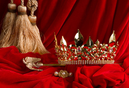 Golden king's crown and scepter on red velvet
