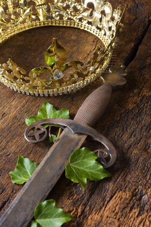 Antieke middeleeuws zwaard en gouden kroon versierd met klimop Stockfoto