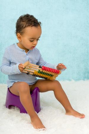 vasino: Formazione Potty di un simpatico africano bambino ragazzo giocando con un abaco