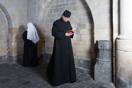 Priester passeren van een jonge non langs de muren van een middeleeuwse abdij