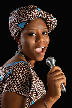 Singing young Ghanese african woman against a black background photo