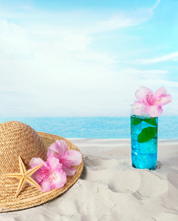 sunhat: Blue longdrink on the beach with a sunhat and sea shells Stock Photo