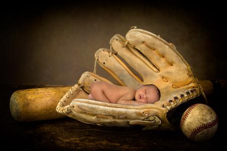 baseball bat: Sleeping newborn baby sleeping in an old baseball glove Stock Photo