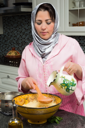 couscous: Moroccan immigrant woman in modern European kitchen preparing couscous for Ramadan nights Stock Photo