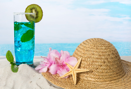 longdrink: Blue drink with green mint leaves and sunhat on the beach