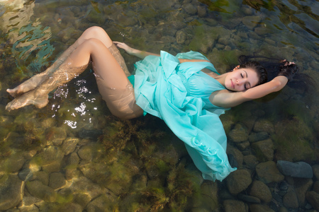 adult mermaid: Beautiful woman in green dress floating in the shallow beach waters Stock Photo
