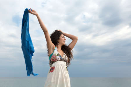 scarf beach: Attractive young woman on the beach waving with a blue scarf Stock Photo