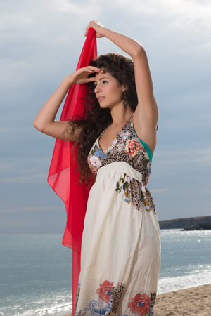 scarf beach: Attractive young woman on the beach waving with a red chiffon scarf