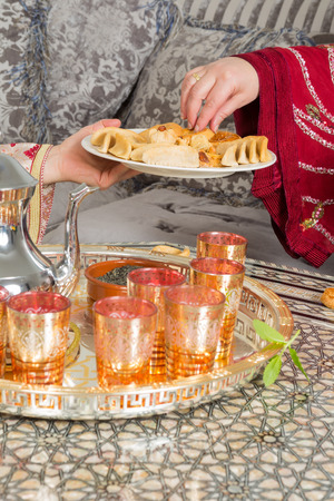 Hands of a moroccan woman presenting ramadan cookies and tea to a guest photo