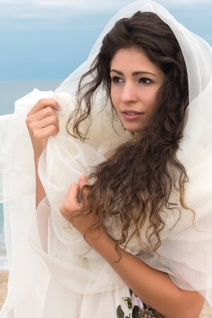 headscarf: Beautiful young woman with long black hair wrapped in a white scarf