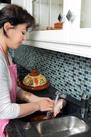 immigrant: Modern Moroccan immigrant woman washing chicken pieces for her traditional tajine dish Stock Photo