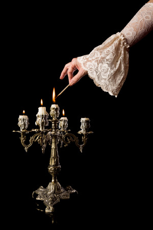 Hand in old-fashioned lace sleeve igniting an antique candlestick