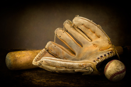 weathered wood background: Dark still life with baseball glove, bat and ball
