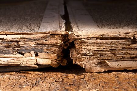 worn paper: Mysterious dark view on the tattered pages of a 300 years old antique gothic book