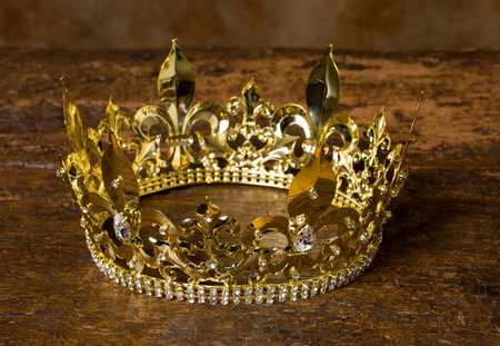 Medieval style golden crown on antique wooden background 写真素材