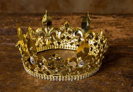 Medieval style golden crown on antique wooden background Standard-Bild