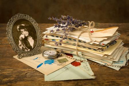 cartas antiguas: Retrato antiguo de una mujer y un manojo de viejas cartas en una mesa de madera Foto de archivo