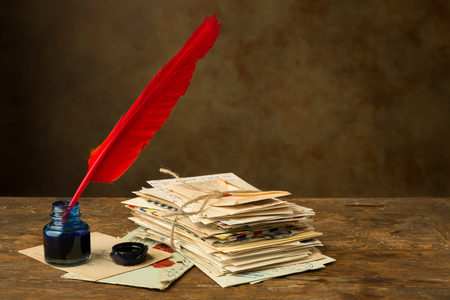 ink well: Red quill feather and ink well lying on an old table with nostalgic letters