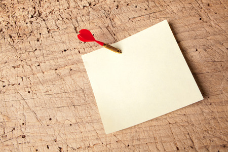 memorise: Red dart in an empty or blank notepad on a vintage wooden board Stock Photo
