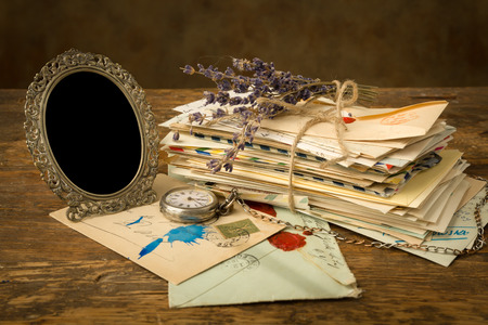 bundle of letters: Empty antique picture frame and a pile of old letters on a wooden table
