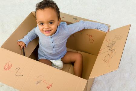 niños negros: Raza mezclada niño pequeño niño que se sienta en una caja de cartón jugando con lápices de colores