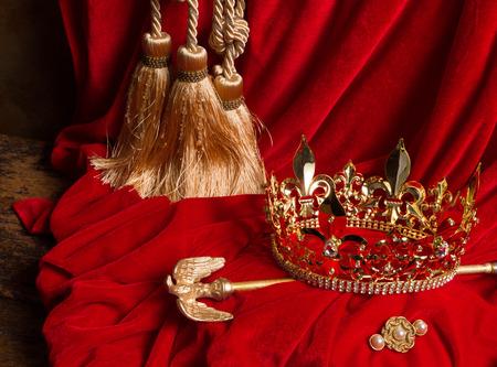 Golden king's crown and scepter on red velvet