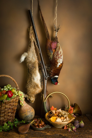 bird feathers: Autumn still life with hunting products, pheasant and hare Stock Photo