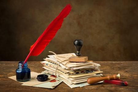cartas antiguas: Pluma pluma y tinta roja, así acostado en una vieja mesa con letras nostálgicas