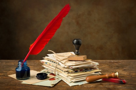 old letters: Red quill feather and ink well lying on an old table with nostalgic letters