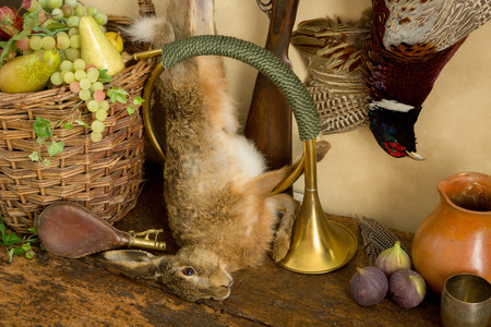 antique rifle: Brass hunting horn and dead hare in an old master hunting still life Stock Photo